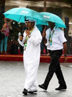 Personas usan paraguas bajo la lluvia en el paddock