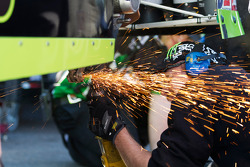 A crew member works on the Monster Energy Toyota