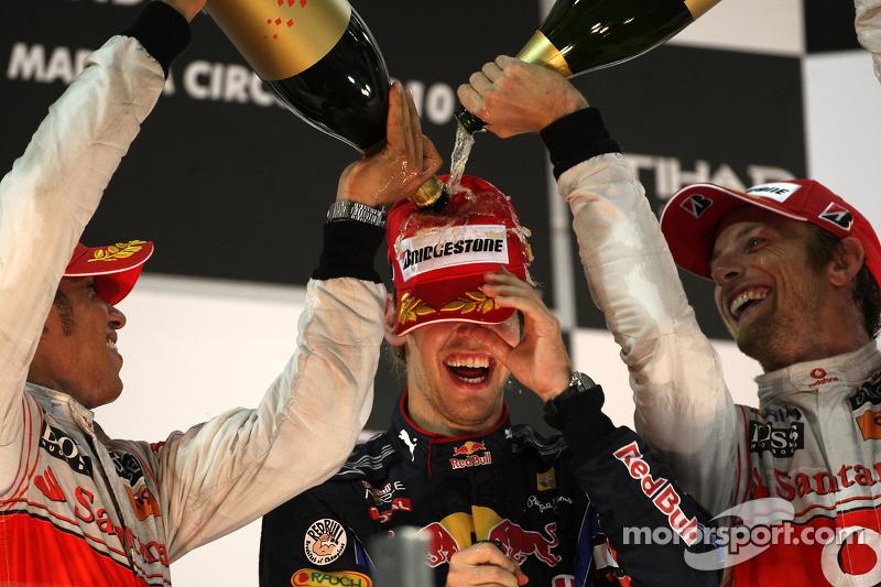 Sebastian Vettel, Red Bull Racing, campeón del mundo de F1 2010, es bañado por Hamilton y Button, de McLaren