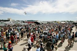 The large Friday crowd watches motorcycle jumpers as they wait for the Champ Car autograph session t