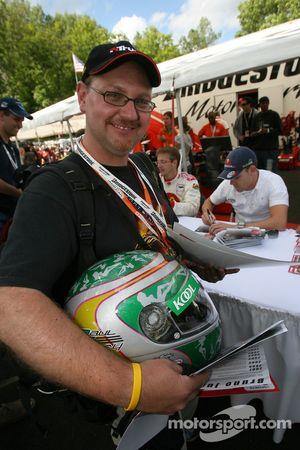 A happy fan with a Paul Tracy helmet