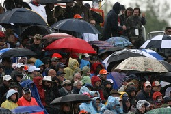 Fans watch the end of the race under the rain