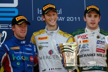 Romain Grosjean celebrates his victory on the podium with Sam Bird and Jules Bianchi