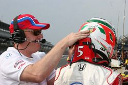 Adrian Fernandez's crew member helps him with his head and neck restraint