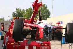Darren Manning's wrecked car returns to the pits on a wrecker