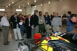 Members of the media look at a partially assembled IndyCar Series car at the Fernandez Racing shop