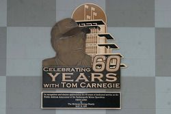The new plaque outside victory lane honoring Tom Carnegie