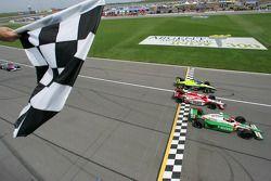 Tony Kanaan takes the checkered flag ahead of Dan Wheldon and Vitor Meira