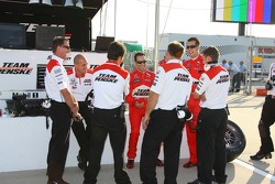 Scott Dixon and Sam Hornish Jr. discuss with Team Penske team members