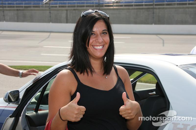 Une jolie fan lève le pouces en l'air après avoir roulé dans la voiture de rythme
