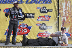 Allen Reinhart laying down on the stage while Antron Brown talks about winning the Southern Nationals