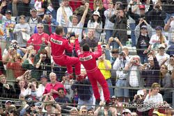 Gil de Ferran and Helio Castroneves climb up the fence