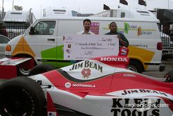 Michael Andretti presents a $5000 check to University of North Texas' health center executive direct