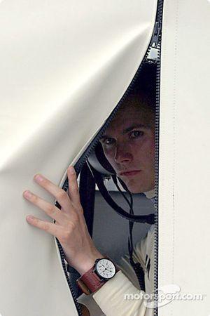 Dan Wheldon peeks out to see if it is still raining