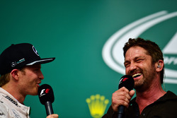 (L to R): Nico Rosberg, Mercedes AMG F1 on the podium with Gerard Butler, Actor