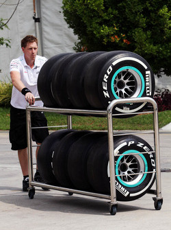 Mercedes GP mechanic wheels Pirelli tyres through the paddock