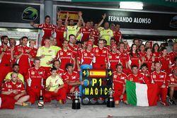 El ganador de la carrera, Fernando Alonso, celebra tras la carrera con el equipo Ferrari
