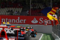 Marshals wave flags as the GP2 cars enter the pit - lane