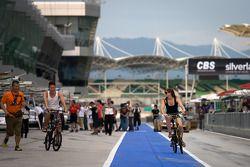 Cyndie Allemann and Akihiro Tsuzuki ride their bikes to track inspection