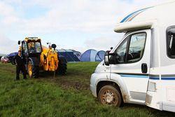 Natte en modderige parking en camping aan het circuit , tractor helpt gestrande camper