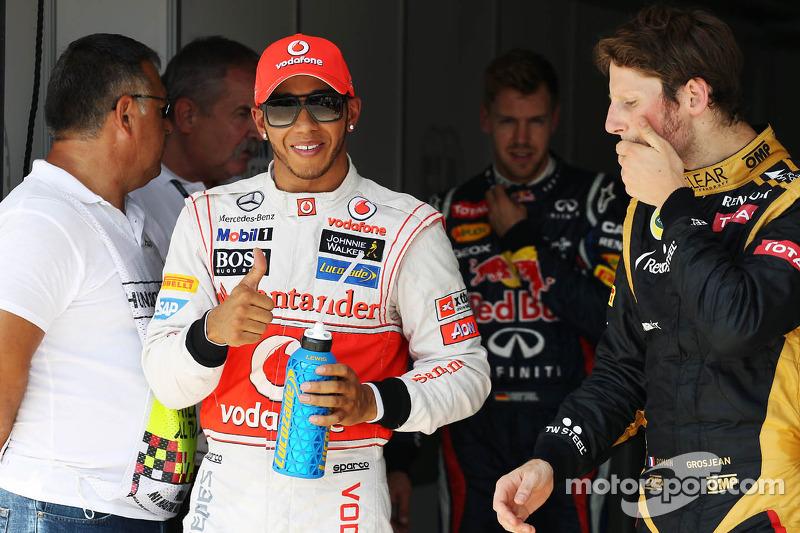 Lewis Hamilton, McLaren, viert polepositie in parc ferme met Romain Grosjean, Lotus F1 Team en Sebastian Vettel, Red Bull Racing