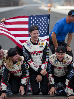 Brad Keselowski and his Penske Racing team members kiss the yard of bricks