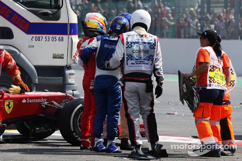 Fernando Alonso, Ferrari es ayudado de su coche después de un accidente al comienzo