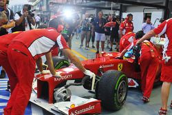 Photographers surround Fernando Alonso, Ferrari as he is pushed back in the pits