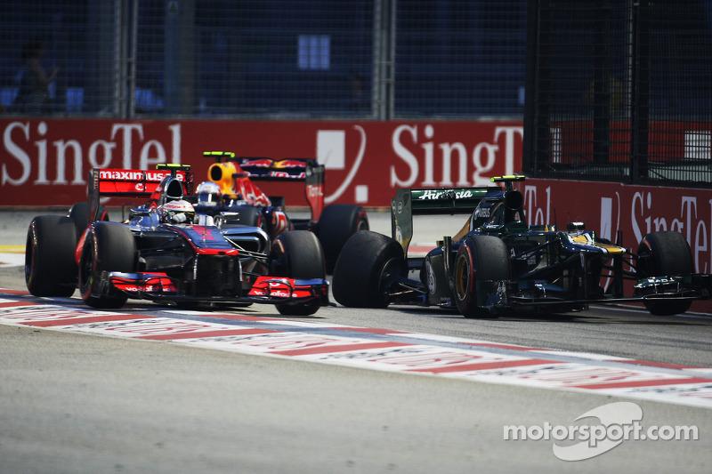 Lewis Hamilton, McLaren y Mark Webber, Red Bull Racing pasean el Caterham chocado de Vitaly Petrov,