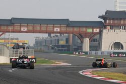 Kimi Raikkonen, Lotus F1 pulls into the pits ahead of Mark Webber, Red Bull Racing