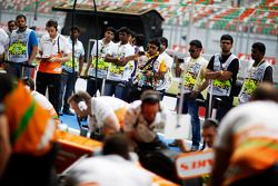 Sahara Force India F1 VJM05 is used to practice pit stops by mechanics ve is watched by pit lane mar
