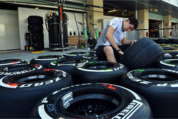 McLaren mechanic prepares Pirelli tyres in the pits