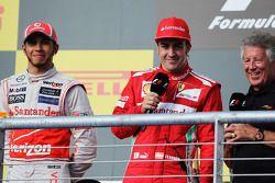 Winnaar Lewis Hamilton, McLaren met Fernando Alonso, Ferrari en Mario Andretti, op het podium