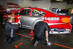 Stewart-Haas Racing Chevrolet crew members work on the wrecked car of Ryan Newman