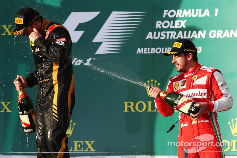 (L naar R): Racewinnaar Kimi Raikkonen, Lotus F1 Team viert feest met Fernando Alonso, Ferrari op het podium