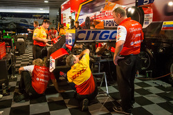 Andretti Autosport team members work on the damaged car of EJ Viso