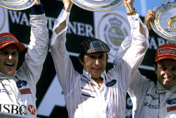 The Stewart Grand Prix team celebrate their first and third places at the European Grand Prix on the podium Team owner Jackie Stewart, centre, with race winner Johnny Herbert, winner, left; and third place Rubens Barrichello