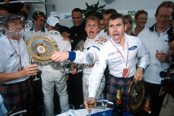The Stewart team celebrate their first GP victory, Jackie Stewart, Johnny Herbert, and Paul Stewart