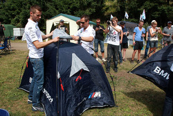 BMW drivers help build tents for fans