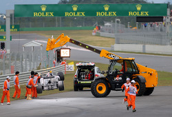 Crews remove Mark Webber's Red Bull from the track after a fire