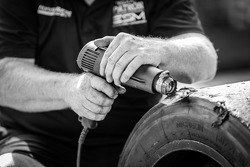 Extreme Speed Motorsports team member scrubs tires