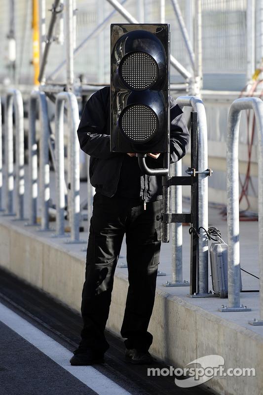 Un trabajador instala las luces en el pitlane