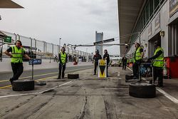 Crew members wait in the pits