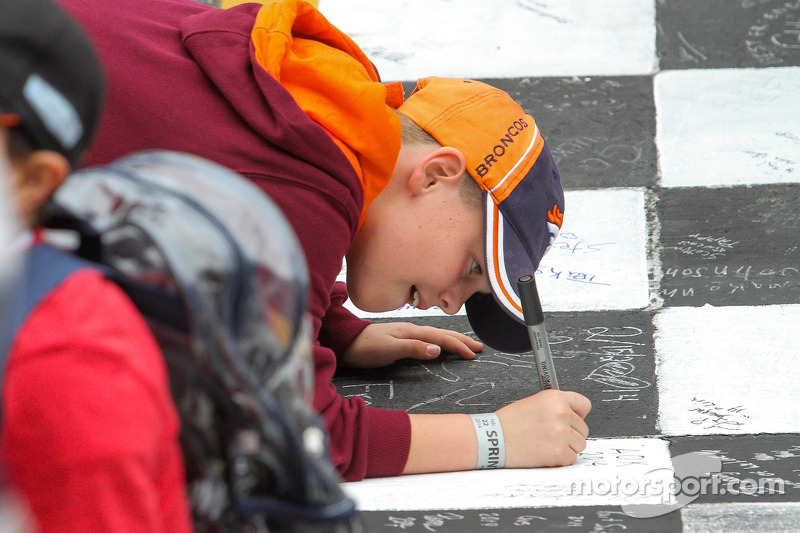 A child draws on the start-finish line