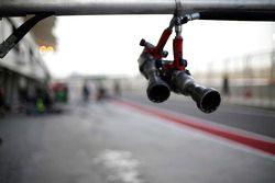 Wheel guns hang from the pit gantry