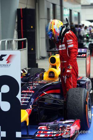Fernando Alonso, Ferrari looks at the Red Bull Racing RB10 of Sebastian Vettel, Red Bull Racing in p