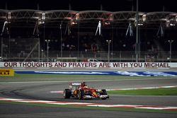 Kimi Raikkonen, Ferrari F14-T pasa la esquina de Michael Schumacher que se muestra un mensaje de apo