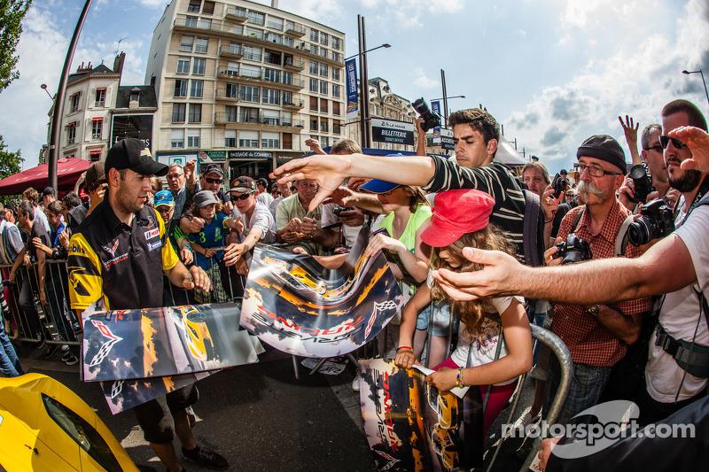 Corvette Racing takım üyeleri taraftarlara poster veriyor