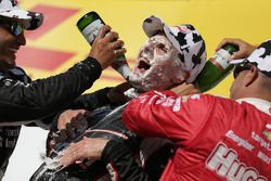 Race winner Will Power gets a face full of cream puff and champagne bath from second place Juan Pabl