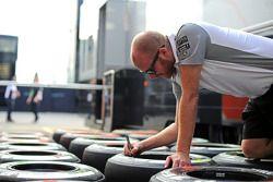 McLaren mechanic marks Pirelli tyres in the pits